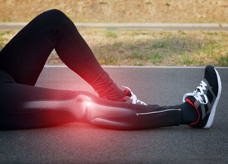 athlete lying on the ground with knee pain