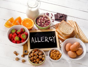 "Sign that says ""allergy"" surrounded by many types of foods that commonly cause allergic reactions"