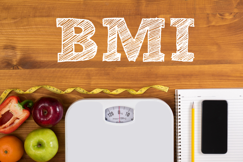 "The acronym ""BMI"" with a scale, healthy food and a notepad underneath."