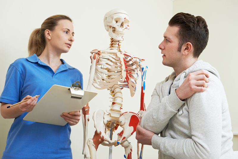 Patient with back and shoulder pain having a chiropractic examination
