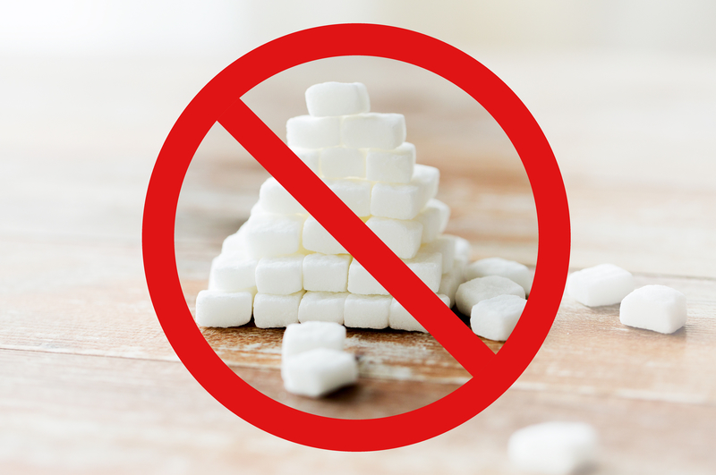 Image of a pile of sugar cubes with a red sign over it signaling no sugar.