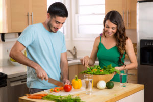 Young couple that is making healthy foods together.
