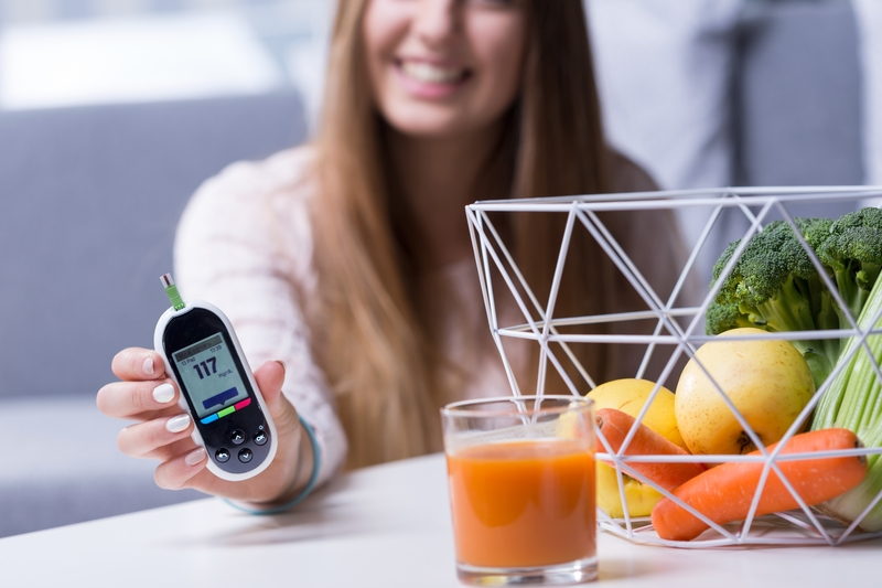 A woman that is holding an insulin reader and she has a healthy smoothie in front of her. She is blurry in the background, while the insulin reader and food is in clear detail in front of her.
