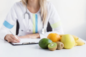 The view of a health professional making notes on a clipboard for a patient. There are healthy foods in front of the health professional.
