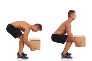 A shirtless man in black shorts that is demonstrating the wrong way to lift a box and the right way.