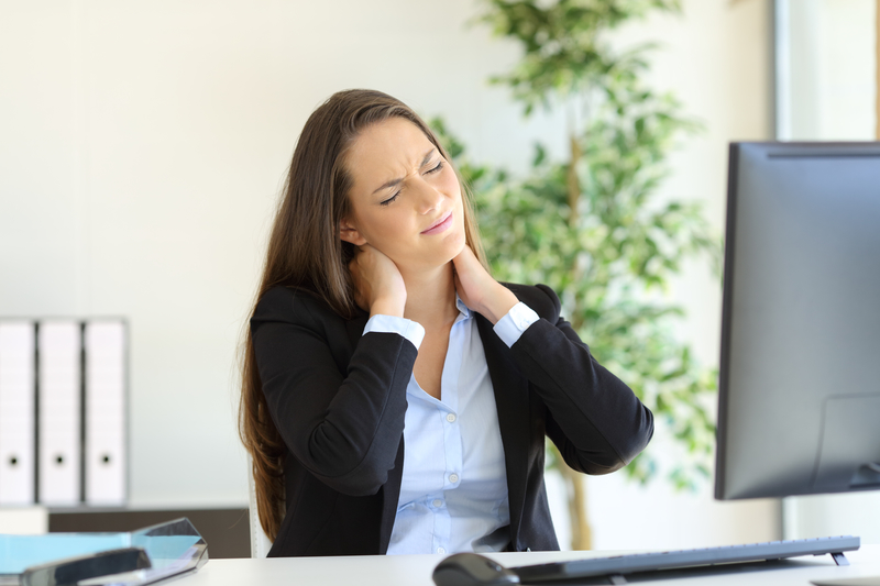 Woman working at a desk that is experiencing neck pain