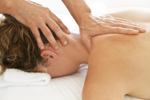 Woman having a chiropractic adjustment done to her neck and upper back