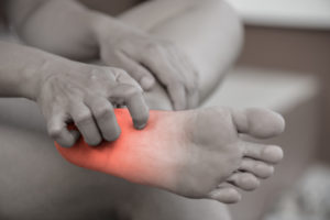 Black and white image of a person holding their foot and their neuropathy area is highlighted in red.
