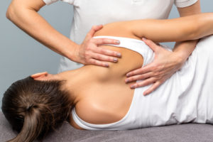 A young adult woman getting a chiropractic adjustment to her back by a chiropractor.