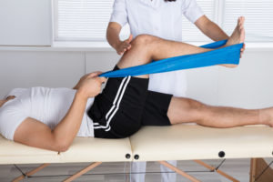 A male patient doing a physical therapy treatment with a chiropractic physical therapist.