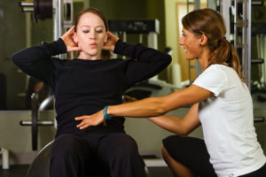 Trainer helping a female patient with proper posture during an exercise in the gym