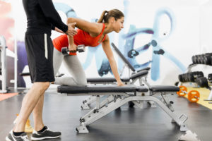 Trainer helping a woman patient in a gym with proper weight lifting posture