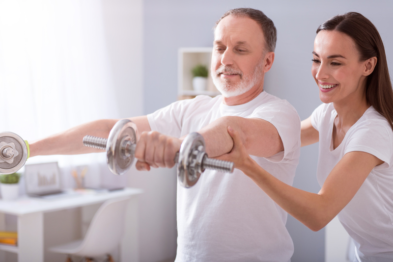 Professional helping an older male patient to have proper weight lifting posture
