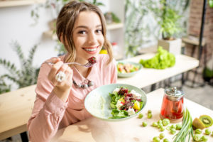 Young adult woman that is smiling and looking at the camera as she eats a healthy salad.