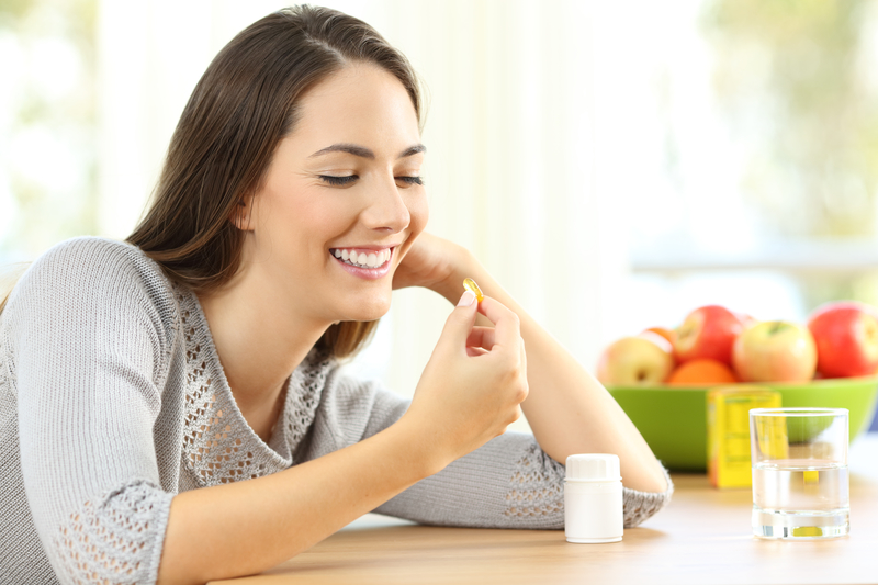 Woman that is sitting at a table with a bowl of apples behind her and she is looking at a vitamin supplement that she is going to take.