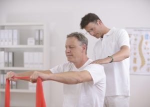 A middle-aged gentleman receiving chiropractic therapy as he uses both hands to pull on a resistance band.