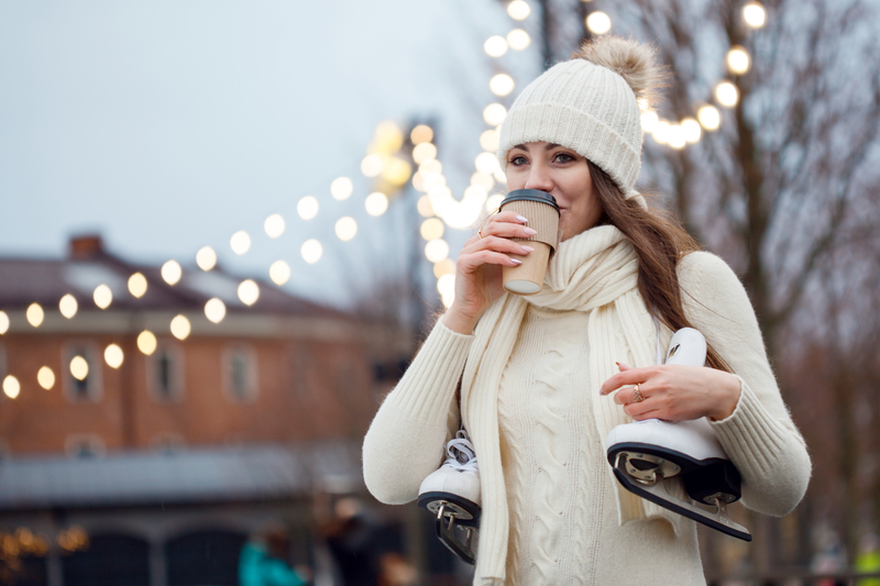 A woman drinking coffee before ice skating. The skates are around the back of her neck and there are Christmas lights behind her.
