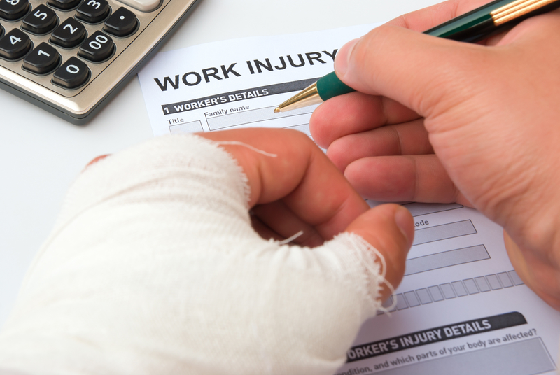 Image that shows a person with a hurt hand filling out a work injury form.