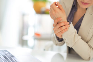 Woman that is at work and holding her wrist that is in pain.