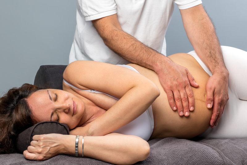 pregnant women getting a back adjustment from a chiropractor